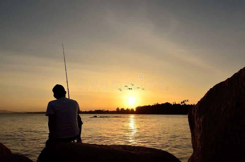Visserssilhouet op het strand stock foto