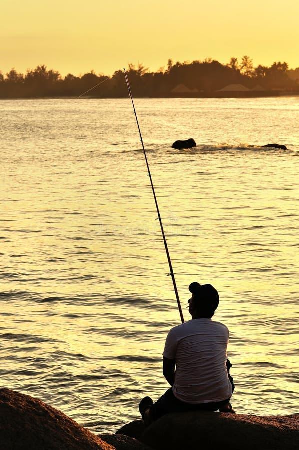 Visserssilhouet op het strand stock foto's