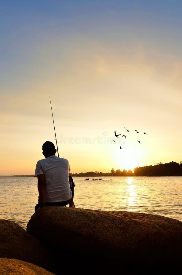 Visserssilhouet op het strand stock afbeelding