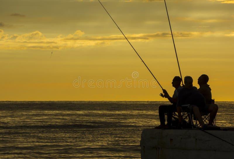 Visserssilhouetten bij de zonsopgang op het dok stock afbeeldingen