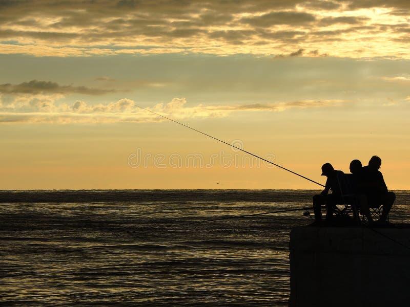 Visserssilhouetten bij de zonsopgang op het dok royalty-vrije stock foto