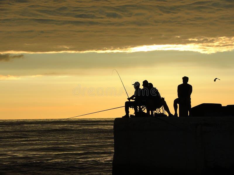 Visserssilhouetten bij de zonsopgang op het dok stock foto