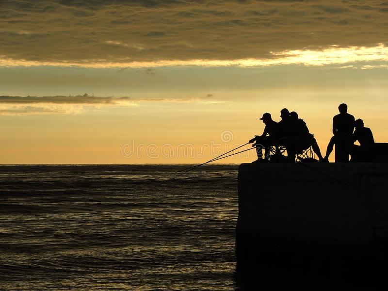 Visserssilhouetten bij de zonsopgang op het dok stock afbeelding