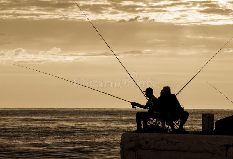 Visserssilhouetten bij de zonsopgang op het dok royalty-vrije stock fotografie