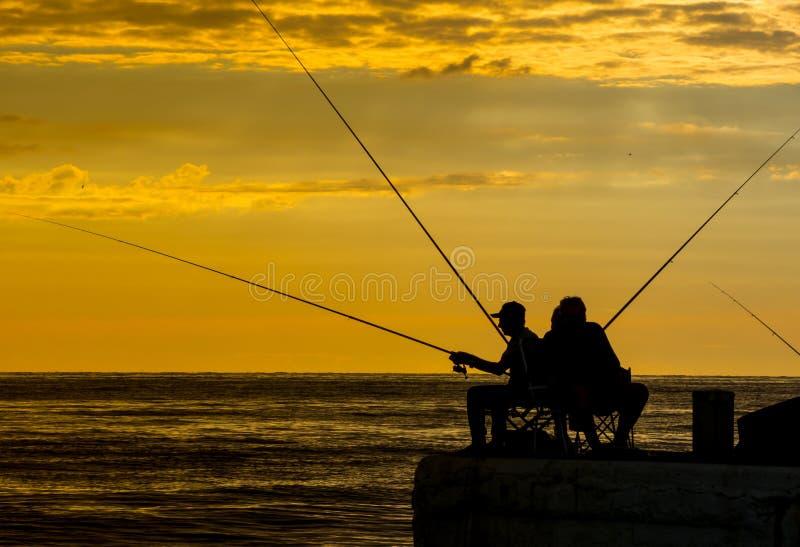 Visserssilhouetten bij de zonsopgang op het dok stock fotografie