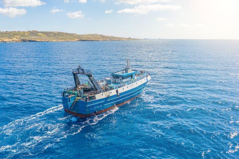 Vissersvaartuigboot die in het blauwe overzees langs de kust drijven stock foto's