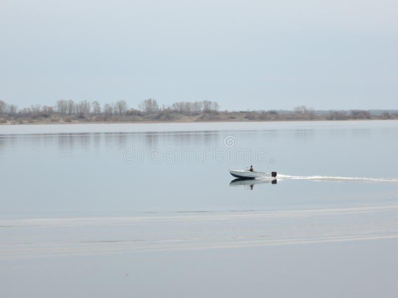 Visserszeilen op boot het snijden door de waterspiegel in de vroege lente stock foto's