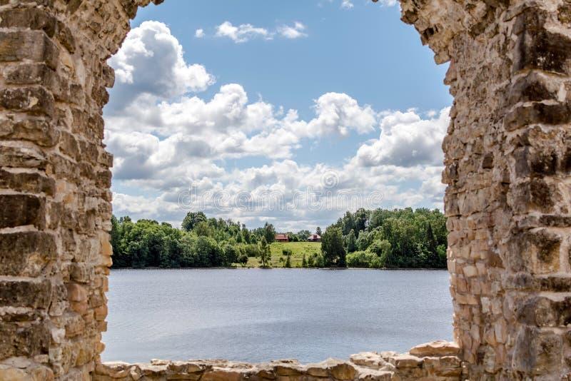 Vista à casa de campo rural no banco de rio com as ruínas do castelo de Koknese fotografia de stock