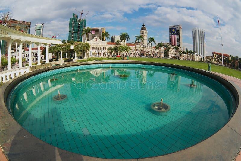 A vista às construções no quadrado da independência refletiu na fonte em Kuala Lumpur, Malásia fotos de stock royalty free
