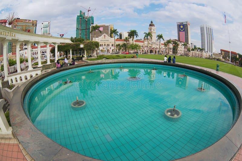 A vista às construções no quadrado da independência refletiu na fonte em Kuala Lumpur, Malásia imagens de stock royalty free
