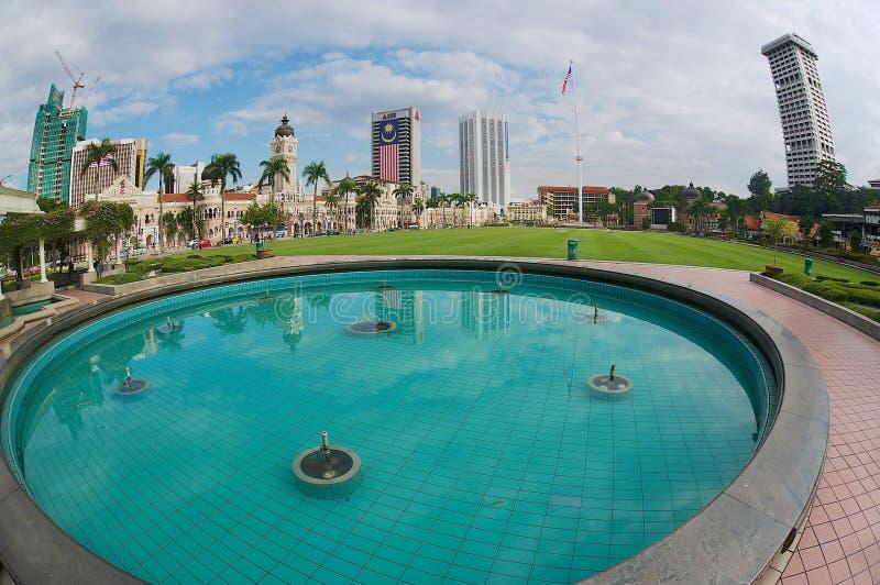 A vista às construções no quadrado da independência refletiu na fonte em Kuala Lumpur, Malásia foto de stock royalty free