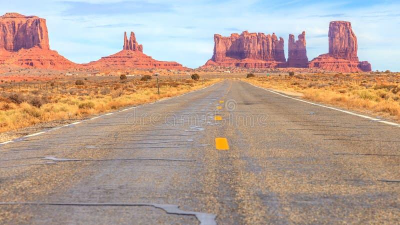 Vista às rochas do alomg do vale do monumento uma estrada no deserto fotos de stock