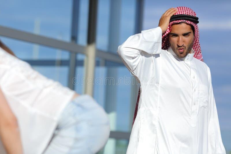 A vista árabe do homem surpreendeu uma extremidade 'sexy' da menina na rua foto de stock