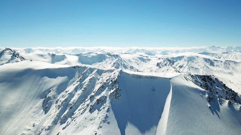 Vista épica de montañas coronadas de nieve Picos de montaña y cielo azul foto de archivo
