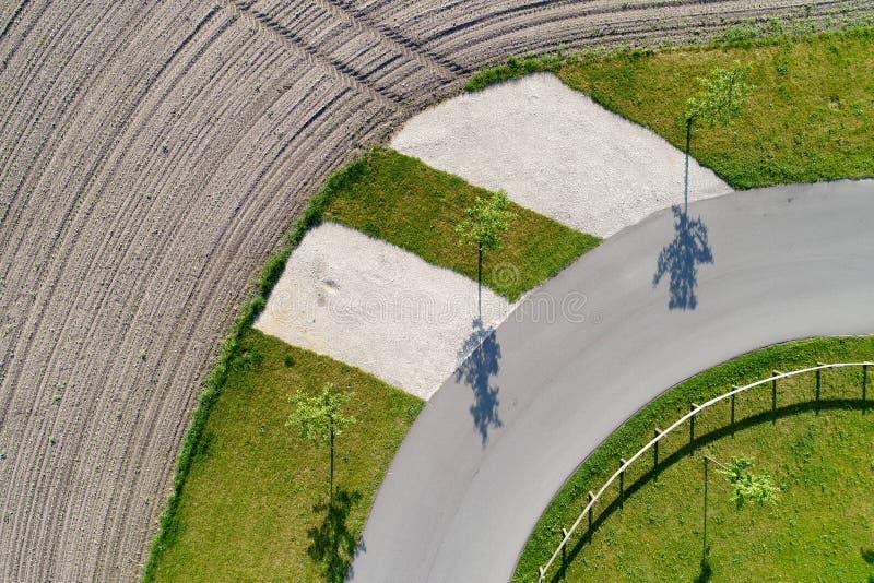 Vista aérea abstracta de la sombra de tres árboles que se colocan en el borde de una curva en una trayectoria al lado de un campo imagenes de archivo