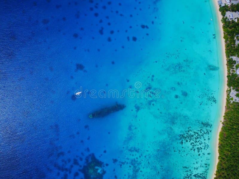 Vista aérea alta de uma destruição afundado do navio de WWII com um iate ancorado e da vila em uma ilha fotos de stock royalty free