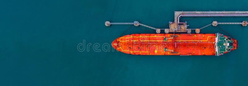 Vista aérea buque cisterna de carga roja en puerto con armas de carga marinas, Comercio mundial sobre el mar y logística comercia imagen de archivo