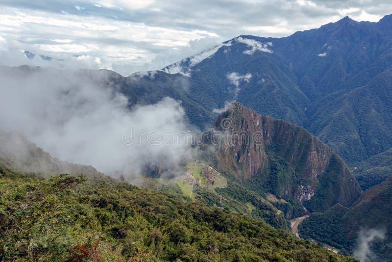Vista aérea da citadela do Inca de Machu Picchu nas nuvens, situada em um cume da montanha acima do vale sagrado fotografia de stock