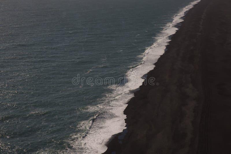 Vista aérea da onda de oceano de Islândia que cresting na praia preta da areia foto de stock