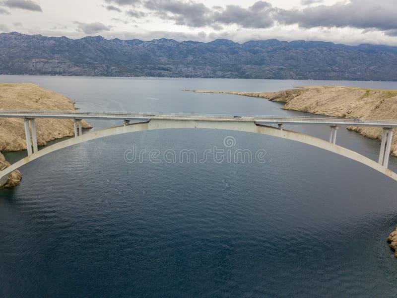 Vista aérea da ponte da ilha do Pag, da Croácia, das estradas e do penhasco croata da costa negligenciando o mar foto de stock