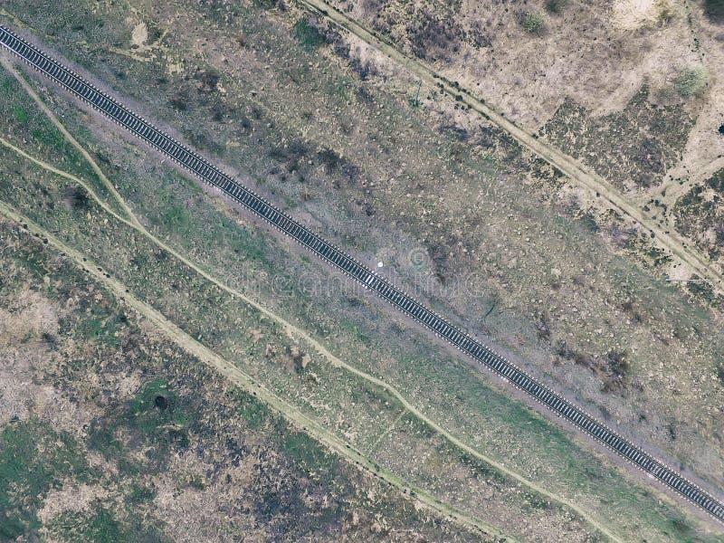 Vista aérea da trilha de estrada de ferro através do campo, opinião superior pov do zangão dos trilhos fotografia de stock royalty free