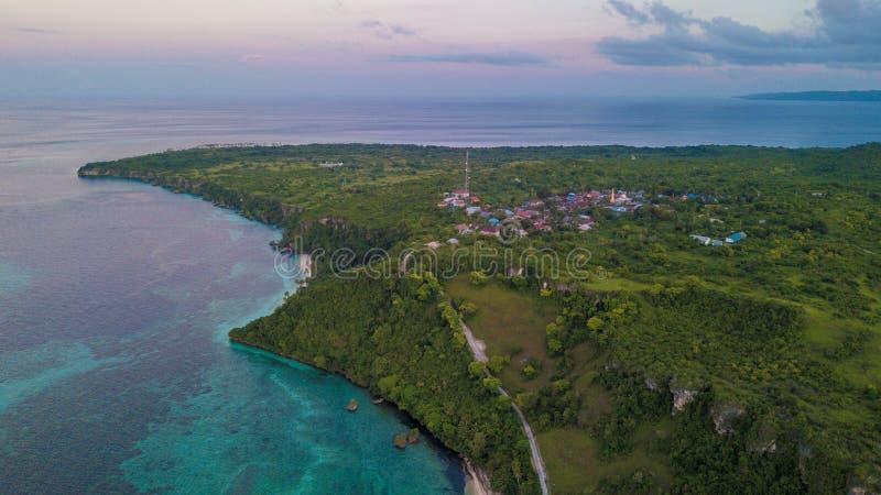 Vista aérea da vila ao lado do oceano azul com o céu agradável do por do sol imagens de stock royalty free