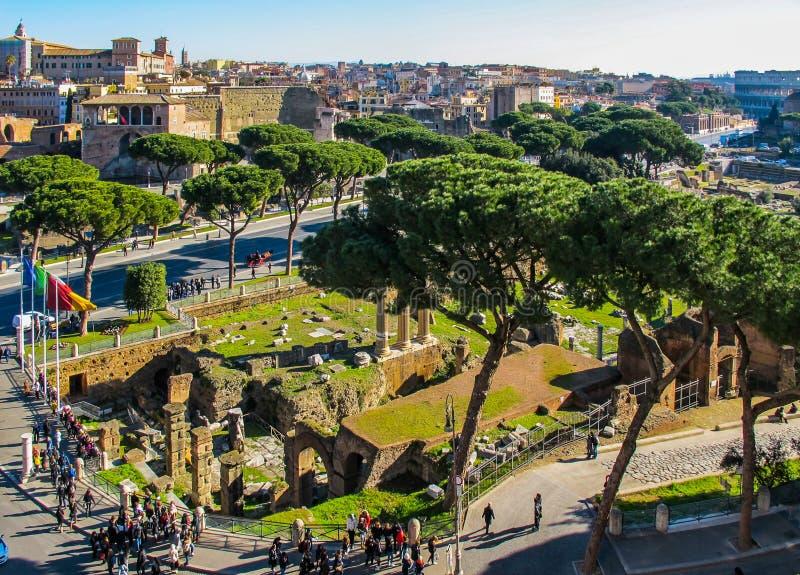 Vista aérea das construções históricas romanas, de ruínas antigas, de coliseu e da rua imperial dos fóruns através do dei Fori Im foto de stock