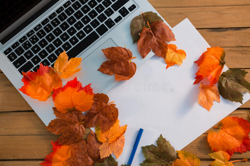 Vista aérea das folhas de outono com papel pelo portátil foto de stock