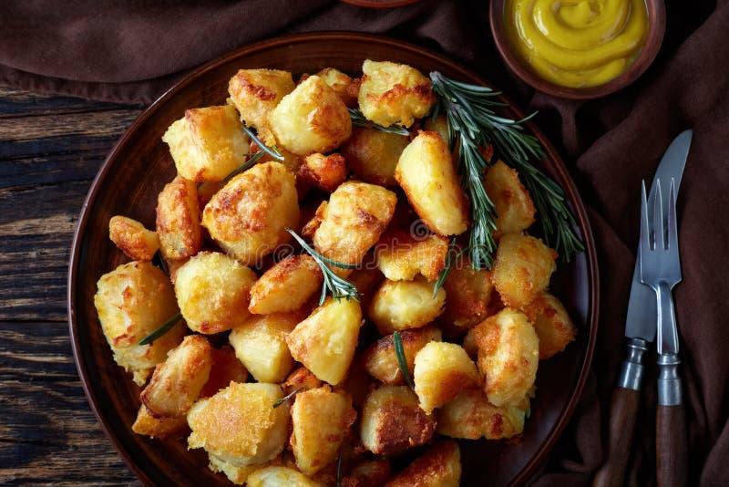 A vista aérea de batatas Roasted friáveis com especiarias e alecrins serviu em um prato da argila com molho da mostarda e de toma foto de stock