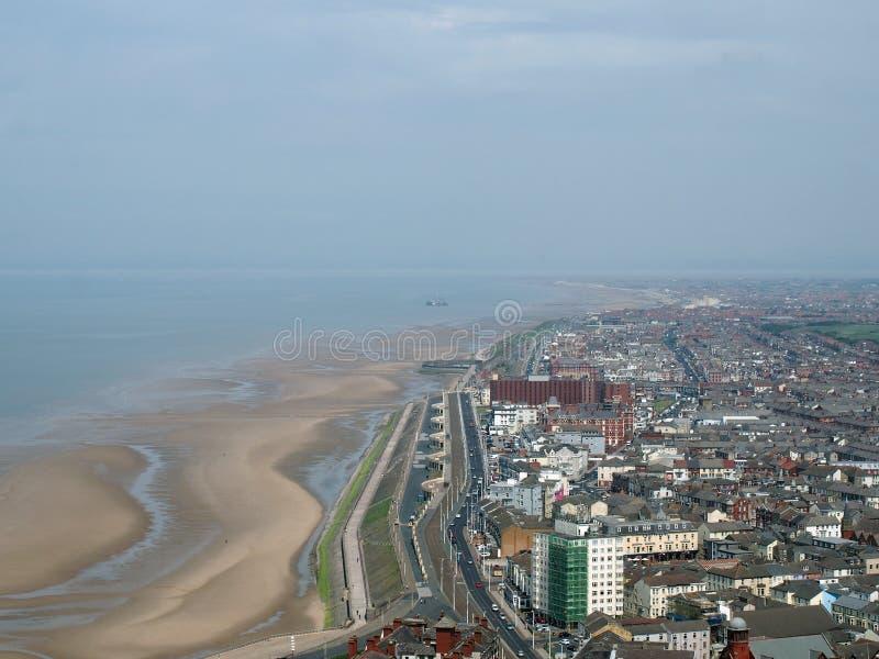 Vista aérea de Blackpool que olha a exibição sul a praia na maré baixa com as estradas e as construções da cidade e da costa fotografia de stock