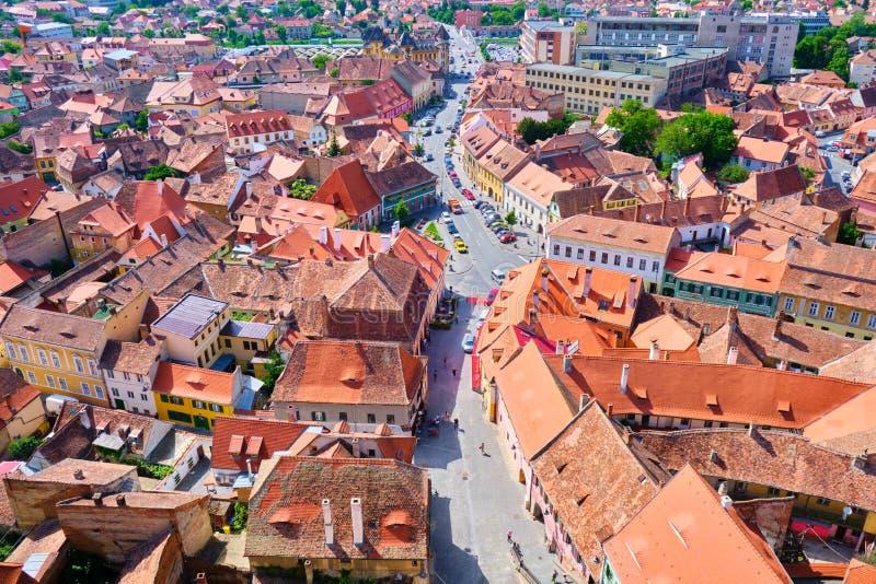 Vista aérea de casas tradicionais de Sibiu com telhados marrom-alaranjados e uma rua no meio, perto da área pedestre da cidade/ce foto de stock
