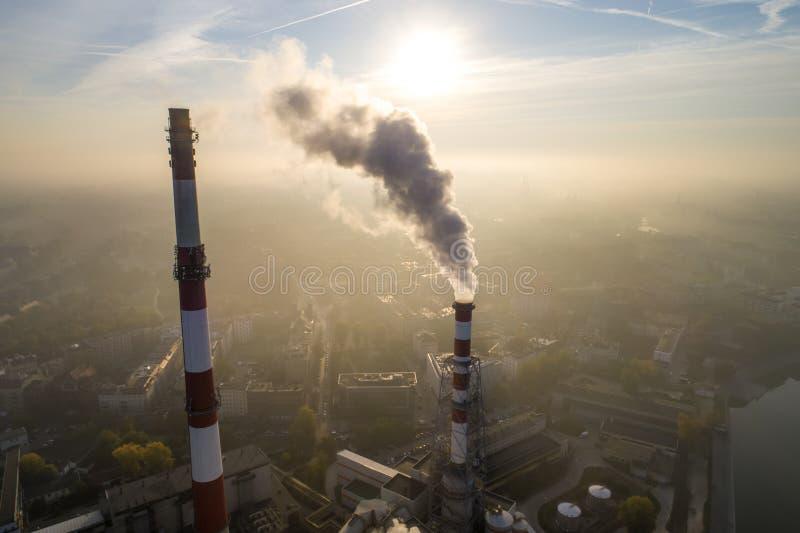 Vista aérea de chaminés de fumo da planta e da poluição atmosférica do CHP sobre a cidade e de builidings no fundo foto de stock