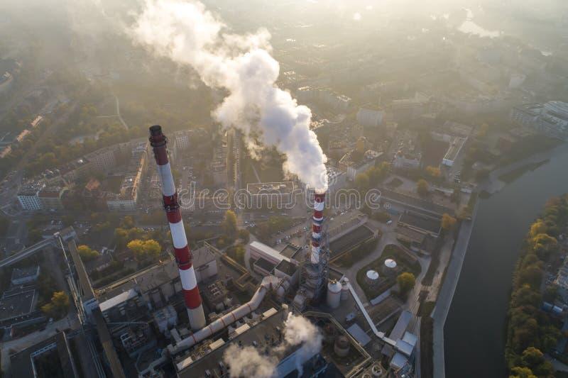 Vista aérea de chaminés de fumo da planta e da poluição atmosférica do CHP sobre a cidade e de builidings no fundo foto de stock royalty free