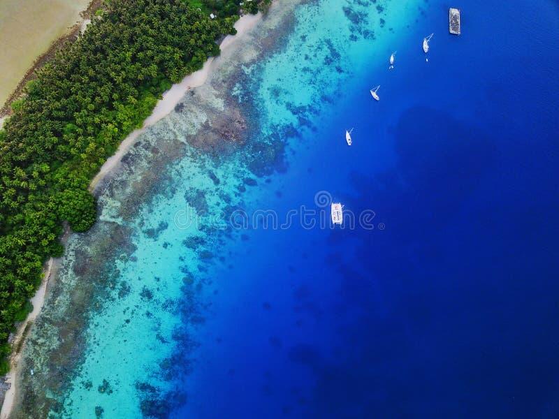 Vista aérea de cinco iate amarrados dentro de um atol tropical vibrante atrás de uma ilha na água pristine, clara imagens de stock