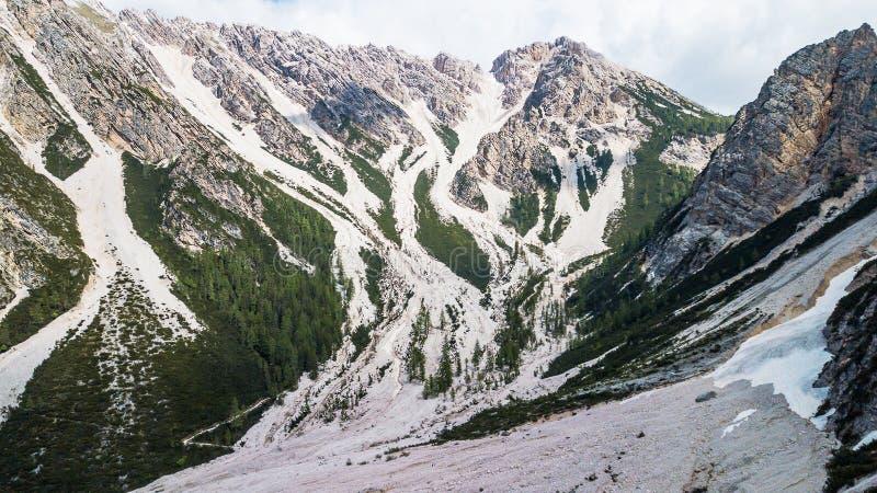 Vista aérea de la corriente de barro con la nieve alta en las montañas alpinas fotografía de archivo