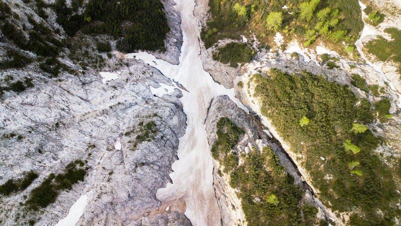 Vista aérea de la corriente de barro con la nieve alta en las montañas alpinas, visión superior fotos de archivo