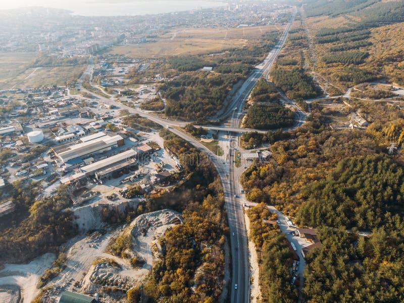 Vista aérea de la infraestructura de las carreteras de asfalto en la raíz de una montaña imagen de archivo libre de regalías