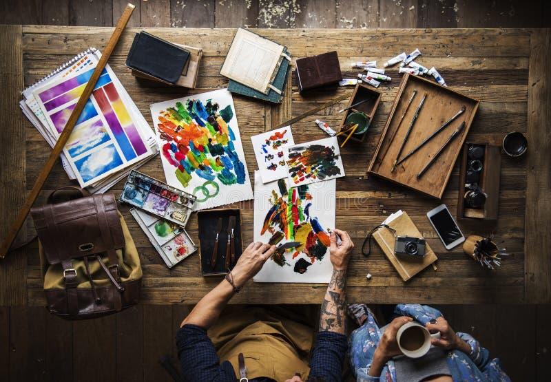Vista aérea de la mano que trabaja con la espátula con la pintura acrílica en p foto de archivo