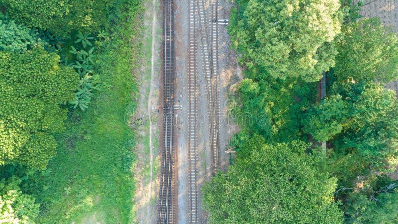 Vista aérea de la pista ferroviaria a través del campo, vista superior pov de carriles como fondo abstracto imagenes de archivo