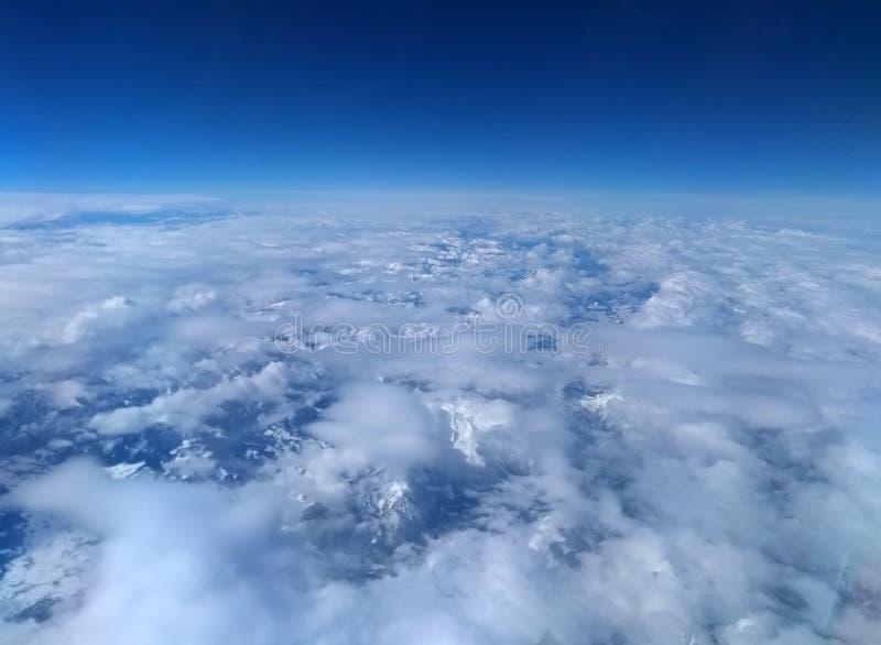 Vista aérea de las montañas nevadas alpinas cubiertas en las nubes blancas y cielo azul profundo imagen de archivo libre de regalías
