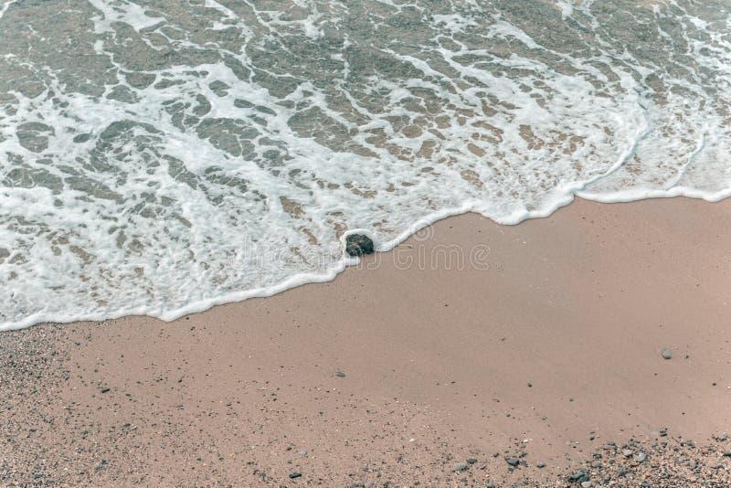 Vista aérea de las ondas que inundan una sola roca fotos de archivo