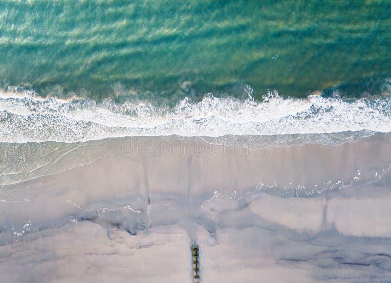 Vista aérea de las ondas que salpican la playa arenosa imagen de archivo