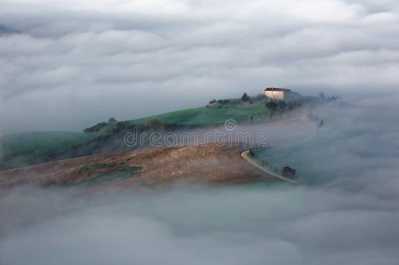 Vista aérea de los cortijos de la cumbre y de los árboles de ciprés en Toscana en una mañana de niebla de la primavera ~ imagenes de archivo