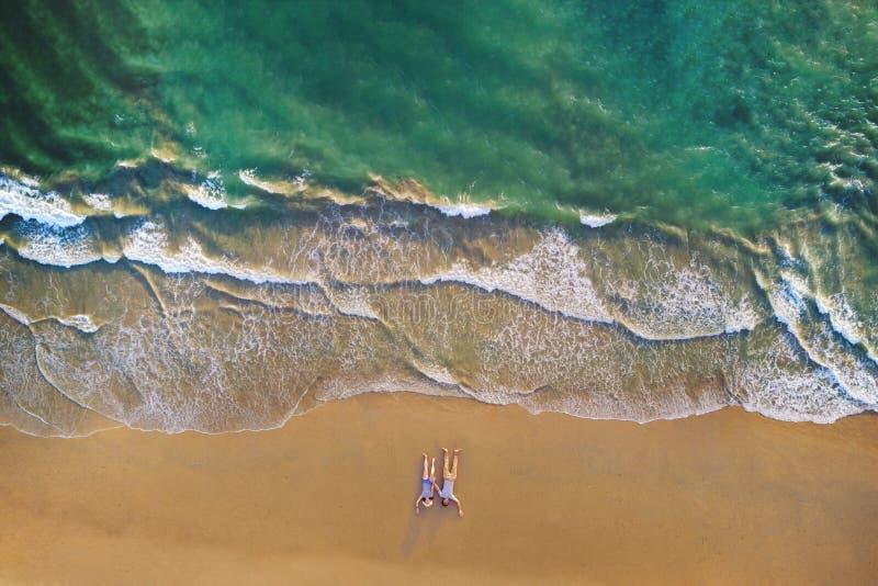 Vista aérea de los pares asiáticos que mienten en la playa con las ondas que ruedan en la orilla para el viaje, fondo al aire lib foto de archivo