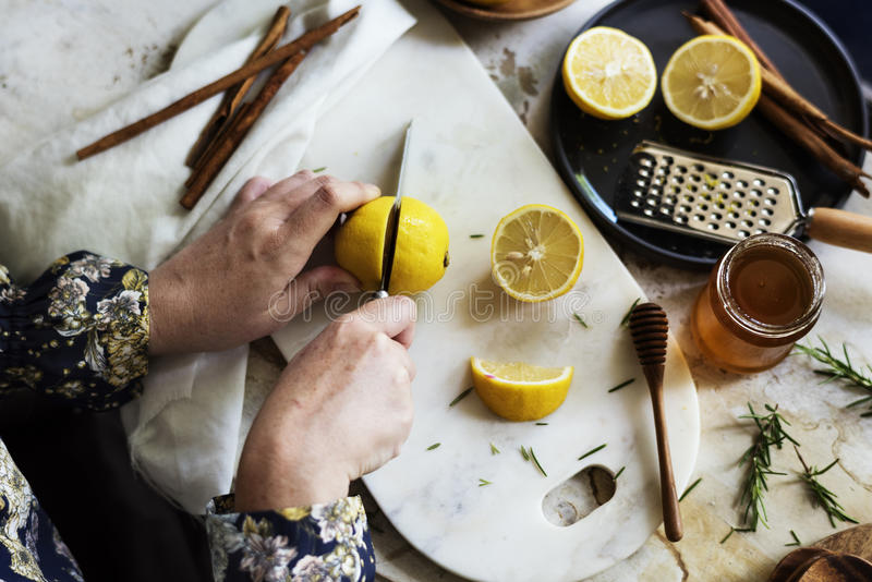 Vista aérea de manos con el limón del corte del cuchillo imágenes de archivo libres de regalías