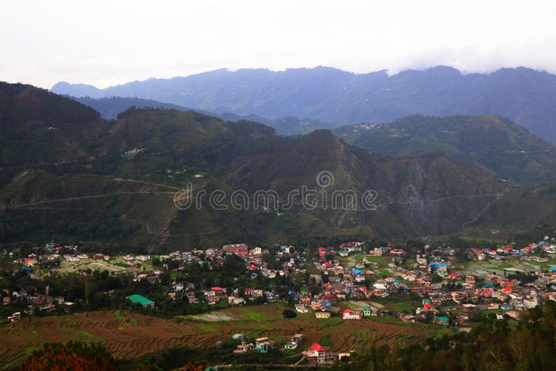 Vista aérea de montes verdes da vila em himachal cercada pela floresta e pelo campo imagem de stock