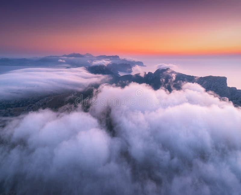 Vista aérea de nubes bajas, de montañas, del mar y del cielo colorido en la puesta del sol fotografía de archivo