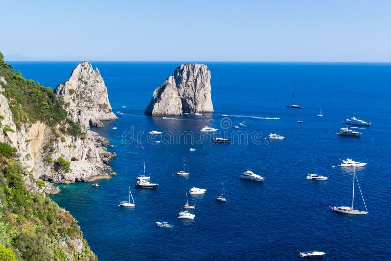 Vista aérea de penhascos famosos de Faraglioni e do mar Tyrrhenian em um dia de verão bonito na ilha de Capri em Itália imagens de stock