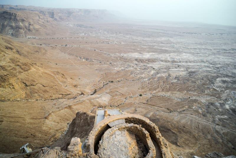 Vista aérea de ruínas da fortaleza do rei Herod contra o vale em montes no deserto de Judean, Israel Sobras do ser humano antigo fotos de stock
