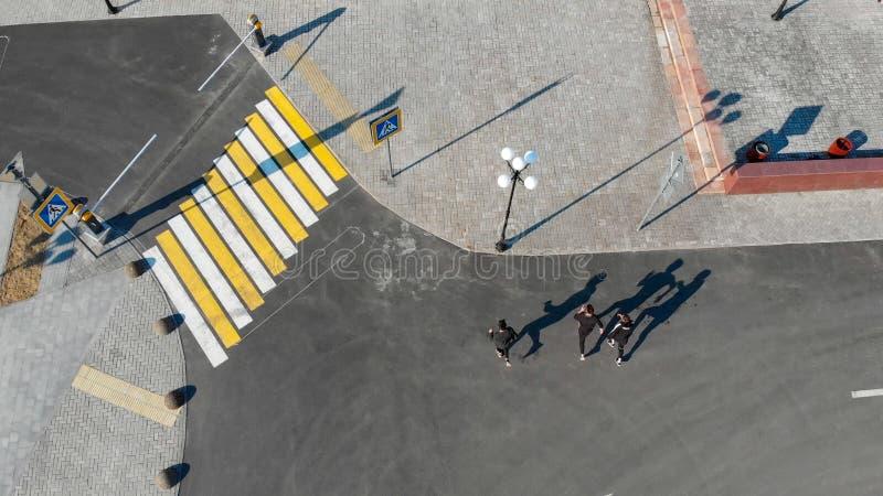 Vista a?rea de ruas urbanas Tr?s homens que andam na estrada foto de stock royalty free